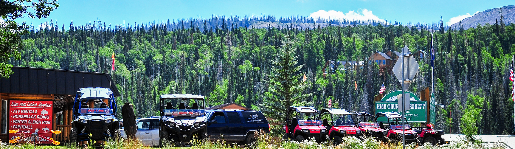 A picture of an activities rental shop surrounded by lush green trees with atv's and cars outside the building near Cedar Breaks Lodge Resort & Spa